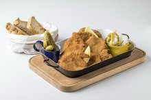 Mix of chicken and pork schnitzels, gherkin, pickled hot pepper, bread from our oven