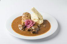Traditional Czech beef goulash with red onion, bread and bacon dumpling